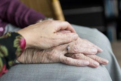 Eine Hand die eine andere berührt und Tröstet. Die Betreuer in unseren Altenheimen in Polen nehmen sich Zeit für die Senioren.