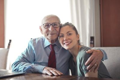 Senior aus Berlin Pankow im Altenheim in Polen sitzt mit seiner Tochter am Tisch.